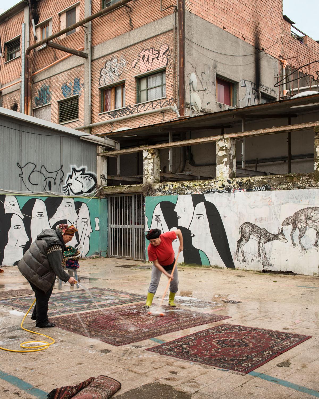 Cortile esterno. Due donne lavano i tappeti. Sullo sfondo le donne che guardano dalla serratura di Alina Vergnano a fianco a quello di hope/gig - Foto di Giuliano Ottaviani