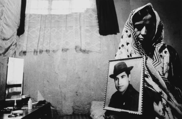 donna in Afghanistan mostra la foto del marito ucciso