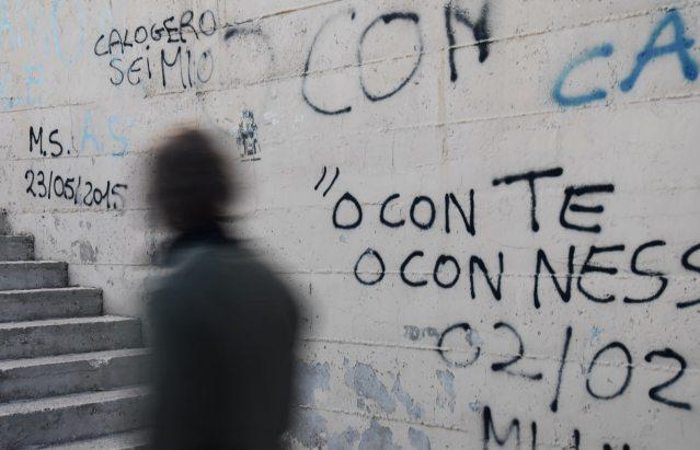uomo cammina lungo un muro con una scritta